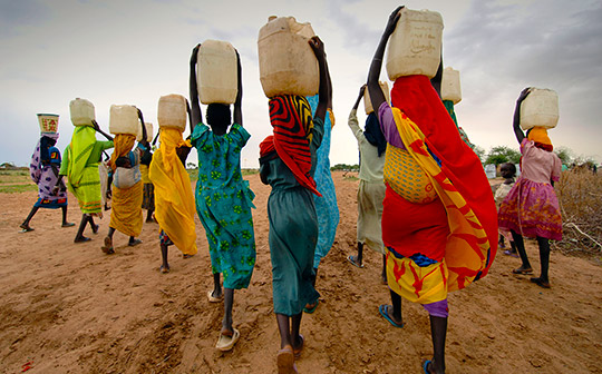 A group of women carrying water