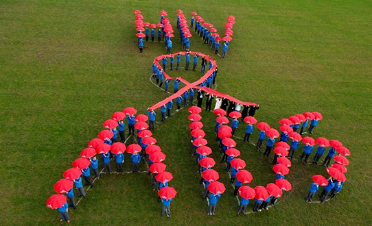 Group of School Children with red umbrellas spelling out an AIDS message